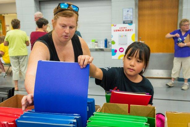 woman helping child pick out blue school folder