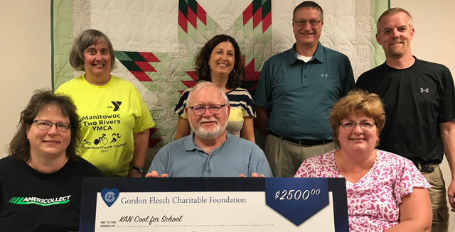 4 people standing and four people sitting behind an oversized check