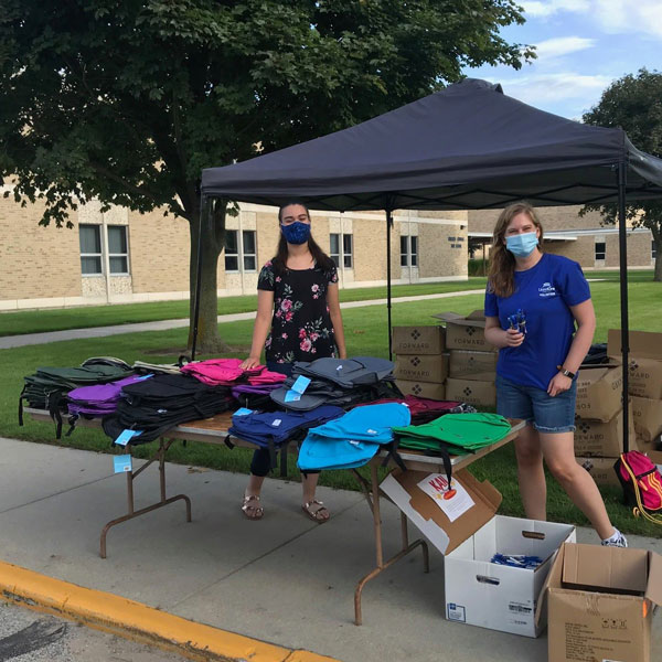 Two female school drive volunteers standing outside behind a table filled with backpacks