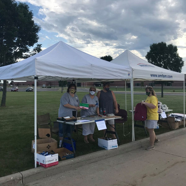 Four volunteers under tents with table full of school supplies