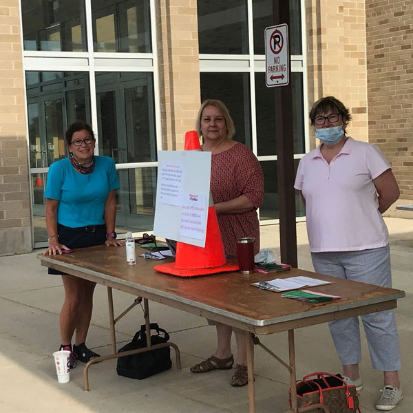 Three female volunteers outside in front of table with orange cone